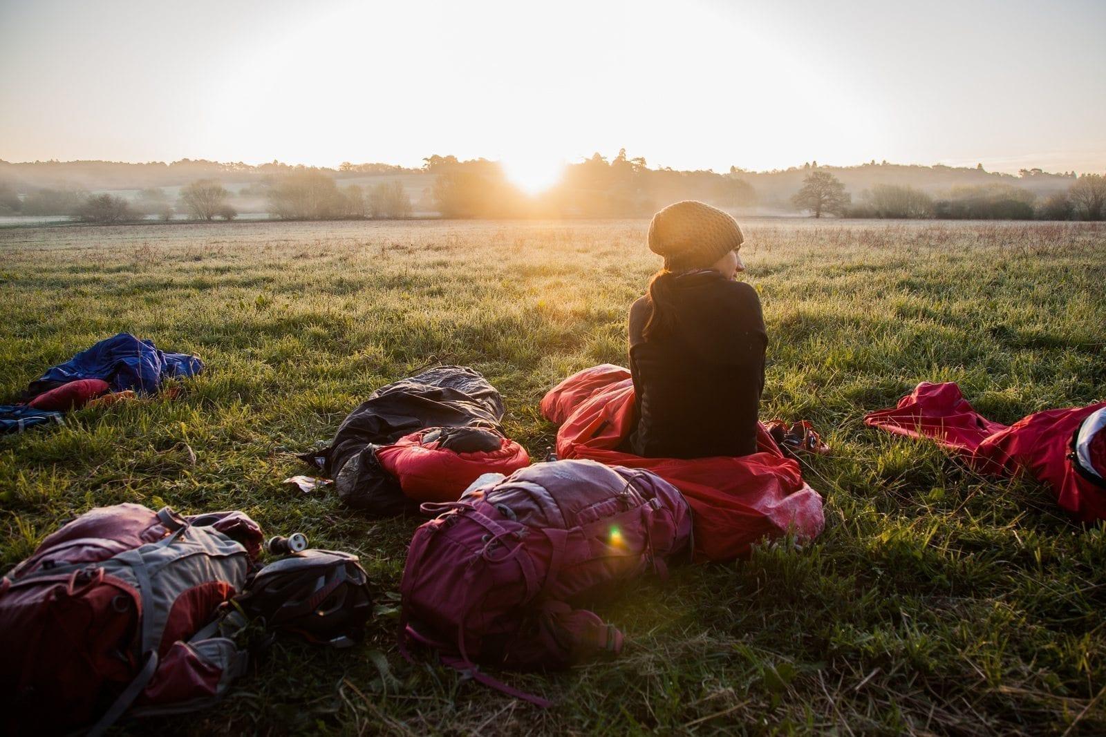 microadventure bivvy girl sunrise field